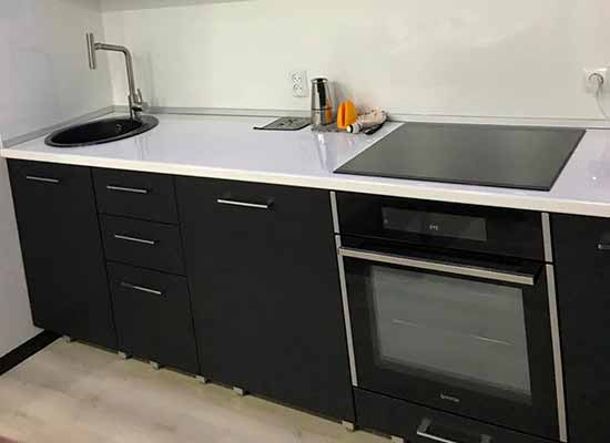 Фото Кухня прямая черная с белой столешницей и черной техникой